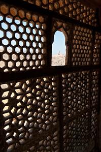 Moucharabieh au Fort d'Amber, siège originel du pouvoir royal et un des plus beaux édifices du Rajasthan. La forteresse d'Amber, depuis le 12e siècle, était la citadelle des Kachwahas et est restée leur capitale jusqu'à ce que le maharaja Sawai Jai Singh II la transfère à Jaipur. L'influence moghole est évidente dans les pavillons ouverts et les jardins emménagés avec canaux et fontaines (et moucharabiehs). Les cours sont entourées de luxueux palais, de halls d'audience et d'appartements. C'est un dispositif de ventilation naturelle forcée fréquemment utilisé dans l'architecture traditionnelle des pays arabes. La réduction de la surface produite par le maillage du moucharabieh accélère le passage du vent. Celui-ci est mis en contact avec des surfaces humides, bassins ou plats remplis d'eau qui diffusent leur fraîcheur à l'intérieur de la maison. Le moucharabieh est aussi souvent présent dans les palais à côté des portes dérobées menant dans des antichambres. Issu de l'architecture islamique, il sert essentiellement à dérober les femmes aux regards. Constitué généralement de petits éléments en bois tourné assemblés selon un plan géométrique, souvent complexe, le moucharabieh forme un grillage serré dont sont garnis les fenêtres, loggias et balcons, appelés alors ainsi par synecdoque. Cette technique elle-même, qui est également utilisée pour la fabrication de meubles, est également appelée ainsi.