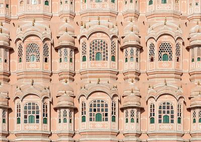 Le Hawa Mahal, littéralement ''palais des vents'', a été construit en 1799. Cet étonnant édifice (Curieux en effet car réduit seulement à une façade! En effet le monument n'a pas de ...profondeur! Tout en haut la largeur n'excède pas les 3 mètres) est l'un des symboles de la ville de Jaipur et de l'art architectural du Rajasthan. Il servait aux femmes du harem royal à observer la rue, à laquelle elles ne pouvaient accéder. Son nom lui vient de sa construction particulière qui laisse passer le vent et la fraîcheur à l'intérieur du bâtiment. Le palais a cinq étages, et il est construit dans la fameuse pierre rose de Jaipur, elle-même surnommée la ville rose. La façade qui donne sur la rue se compose de 950 fenêtres, et le vent qui se glisse dans les petites ouvertures crée un bruit spécifique qui a valu son nom au palais.