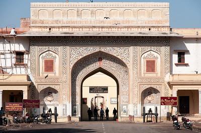 """La porte du City Palace de Jaipur. Palais de ville du Maharaja en grès rose et en marbre blanc, transformé en musée par le dernier maharaja. Construit par Maharaja Sawai Jai Singh II (1686-1743), pendant son règne, cette grande structure de 7 étages contient entre autres une belle collection d'armes du 15e et de costumes. Le Palais se tient à part, avec son architecture remarquable, mélange d'art moghol et râjasthâni. Le complexe de Palais de ville occupe une vaste surface (1/7e de la superficie de la ville fortifiée), qui est divisée en une collection de jardins, de cours et de bâtiments. Une partie du Palais est toujours habitée par le Maharaja actuel (les plus belles parait-il ?) : Son Altesse Bhawani Singh""""Bubbles"""", fils de Man Sing II (1922-1970), dernier Maharaja, très populaire, qui fut nommé « Rajpramukh » (gouverneur) de l'état après l'Indépendance. Actuellement, il y aurait encore 350 employés au palais !"""