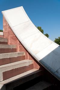 """Détail d'un instrument du Jangar Mantar -une altération du mot sanscrit Yantrasala , signifiant """"Instruments à formule ésotérique""""-: observatoire de Sawai Jai singh II grand érudit en astronomie et mathématique qui avait déjà construit des observatoires à Delhi, Mathura et Varanesi (Bénares). Peu satisfait des instruments en cuivre, Jai Singh II, à Jaipur, les construit (entre 1728 et 1734) en marbre et en pierre. Ils seront plus précis, et fournissent des méthodes et des mesures (toujours aussi précises de nos jours) pour étudier les mouvements du soleil, de la lune et des planètes, tout en étant d'une beauté abstraite et futuriste. Tous ces instruments dont les noms et les fonctions nous dépassent sont en parfait état de conservation. On peut citer le Samrat Yantra qui mesure l'heure solaire à Jaipur, le Jai Yantra qui mesure la rotation du soleil, le Ram Yantra qui mesure la distance zénithale et l'altitude du soleil et enfin le Yantra Raj, le plus grand astrolabe du monde, énorme disque de cuivre de 2 m de diamètre qui permet de déterminer les dates de fêtes religieuses selon le calendrier hindou. Ici Dakshinodak- Bhittiyantre restauré en 1876, pour rechercher l'altitude du soleil puis la déclinaison et la longueur du jour… à midi. A voir aussi un gigantesque cadran solaire et douze plus petits, un par signe du zodiaque."""
