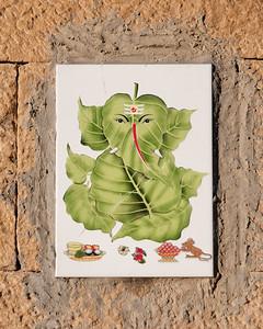 """Représentation en feuille de Ganesh sur céramique murale. Ganesh est l'un des Dieux les plus importants de l'Hindouisme, non par le rang hiérarchique qu'il occupe, car à l'origine il était loin de figurer sur le même """" plan """" que les figures majeures de la Trimûrti (Brahmâ, Vishnu et Shiva), mais bien par son omniprésence dans la vie quotidienne des gens. A telle enseigne que les innombrables fidèles de Ganesh le considèrent comme la Divinité Suprême. Les images de Ganesh dans les jardins publics, sur les trottoirs des rues, sur les bords des ghats, des fleuves, au-dessus des linteaux des portes des maisons, depuis les palais jusqu'aux maisons les plus humbles, se retrouvent partout..."""