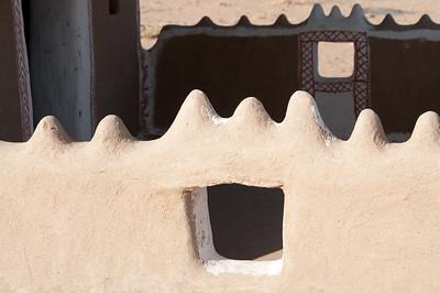 Détail d'une ouverture dans un muret. La maison bishnoï consiste à de petites pièces- cases- (cuisiner, dormir, parents, enfants, familles…) autour d'une cour centrale. Le matériau de construction est en bouse.