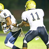 E. E. Smith's Harold Herbin (11) hands the ball off to Tygee Spann (8).Middle Creek rolls over E.E. Smith 56 to 7 Friday night August 30, 2013. (Photo by Jack Tarr)