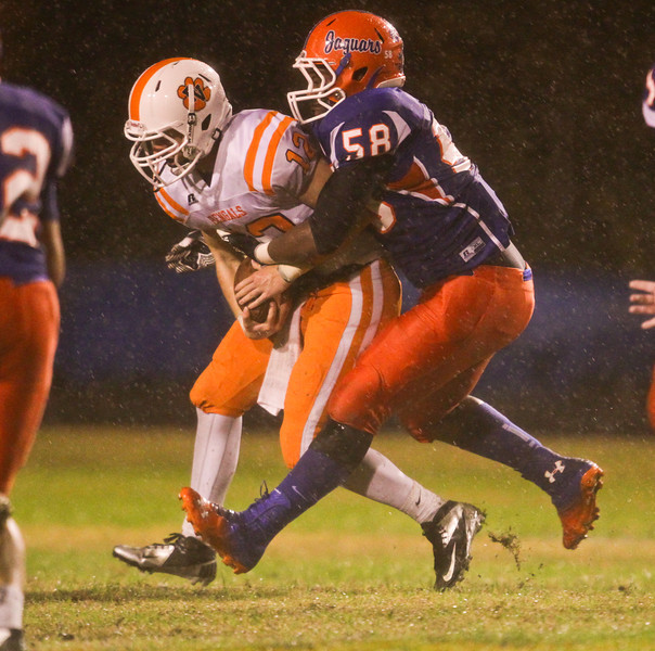 Fuquay's Caleb Mundy (12) is tackled for a loss. Fuquay defeats Athens Drive 24 to 13 Friday night November 1, 2013. (Photo by Jack Tarr)