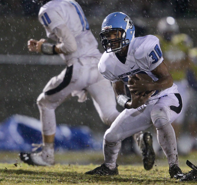 Panther Creek's  Akeem Smith (30) runs the ball. Panther Creek rolls over Holly Springs 27 to 0 Friday night November 1, 2013. (Photo by Jack Tarr)