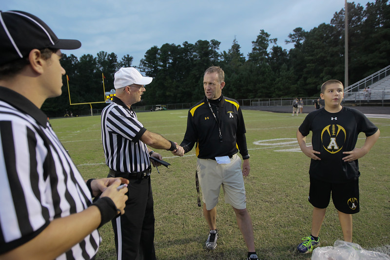 Apex head coach Joe Kilby greets the officials. Apex defeats Fuquay Varina 45 to 35 Friday night October 3, 2014. (Photo by Jack Tarr/WRAL Contributor)