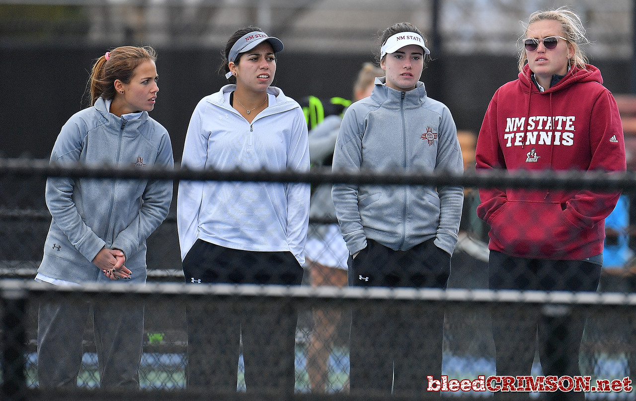 LAS VEGAS, NV - JANUARY 20:  (L-R) Eli Arnaudova, Yadira Rubio, Helena Colvee and student assistant Gabrielle Joyce of the New Mexico State Aggies look on during a match between the New Mexico State Aggies and the Weber State Wildcats at the Frank and Vicki Fertitta Tennis Complex in Las Vegas, Nevada.  Photo by Sam Wasson/bleedCrimson.net