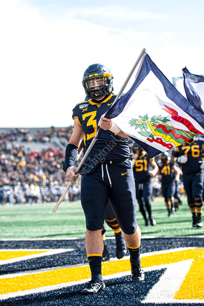 Shea Campbell caries the state flag across the endzone. The Mountaineer Football team faced off against Texas Tech at Mountaineer Field November 9, 2019. (WVU Photo/Parker Sheppard)