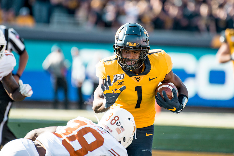 TJ Simmons sticks an arm out to block a Texas defender as he runs the ball down the field. WVU Football faced off against Texas at Mountaineer Field October 5, 2019. (WVU Photo/Parker Sheppard)