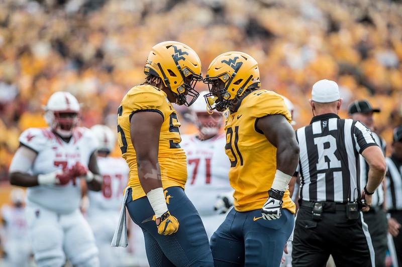 Dante Stills and Reuben Jones stand helmet to helmet. WVU's football team faced off against NC State on September 14, 2019. (WVU Photo/Parker Sheppard)
