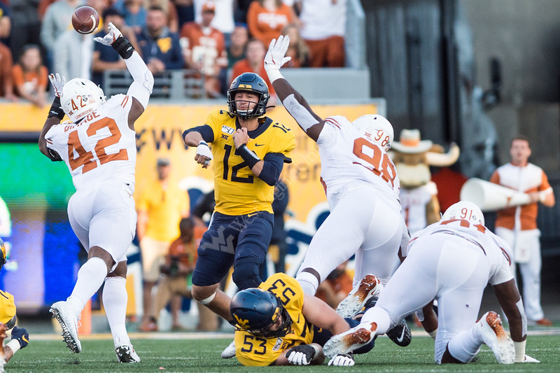 Quarterback Austin Kendall throws the ball across the Texan's defensive line on October 5, 2019. The crowd striped the stadium with blue and gold and the 2019 Homecoming King and Queen was announced on this day the the Milan Puskar Stadium. (WVU Photo/ Hunter Tankersley)