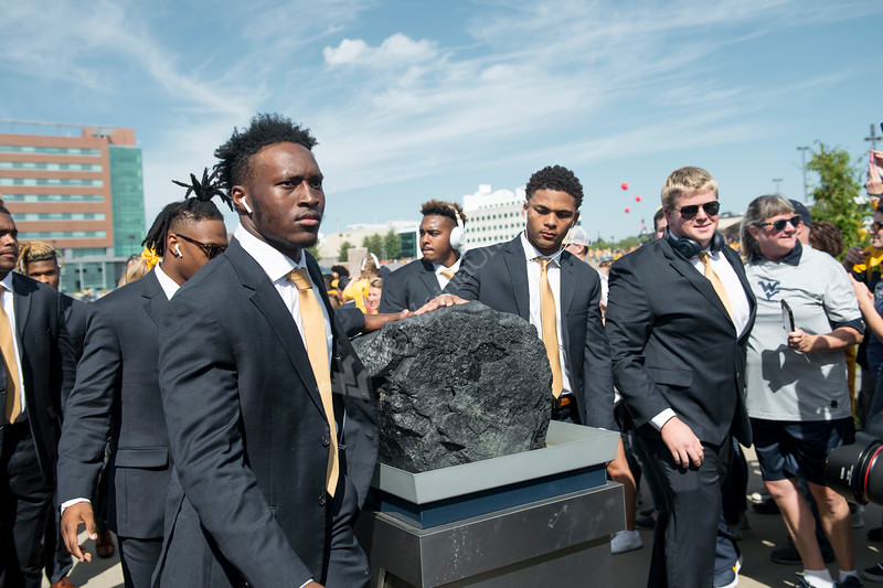 WVU players place their hands on the coal as they enter Mountaineer Field. WVU Football faced off against Texas at Mountaineer Field October 5, 2019. (WVU Photo/Parker Sheppard)