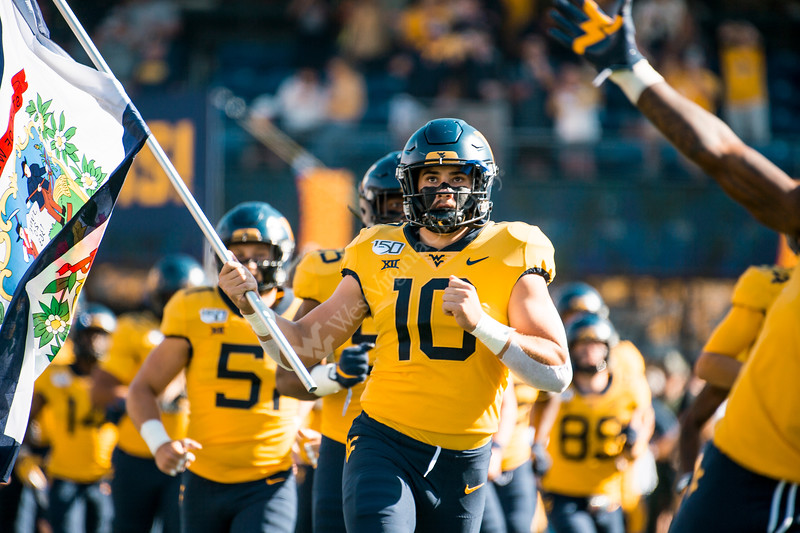 Dylan Tonkery leads the team onto the field with the state flag. WVU Football faced off against Texas at Mountaineer Field October 5, 2019. (WVU Photo/Parker Sheppard)