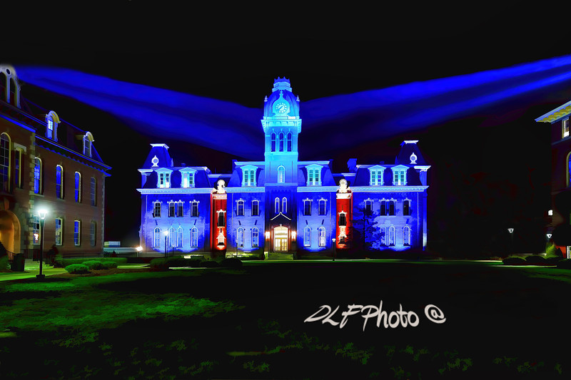 "To purchase - <a href=""http://dan-friend.artistwebsites.com/galleries.html"">http://dan-friend.artistwebsites.com/galleries.html</a><br /> <br /> Following an extensive restoration of the facade and exterior of historic Woodburn Hall in 2011, the traditional holiday lights were replaced by modern and energy efficient LED architectural lighting. To help protect WVU's iconic building for the future, this change was necessary. The new lighting will be used through out the year and and change colors when programmed for the holidays and special occasions. These new lights will help to create new traditions and memories<br /> Woodburn Hall: Woodburn Hall was built between 1874 and 1876, and is a brick Second Empire style building. It has a mansard roof topped by a cupola and clock tower. Wings designed by Elmer F. Jacobs were completed in 1900 and 1911. Its name references Woodburn Female Seminary, a school originally located on the West Virginia University campus."