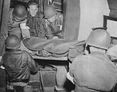 Medical personnel load a litter patient aboard a 442nd Troop Carrier Group C-47 during World War II.  The 442nd was a major air ambulance carrying wounded GIs to hospitals in England.