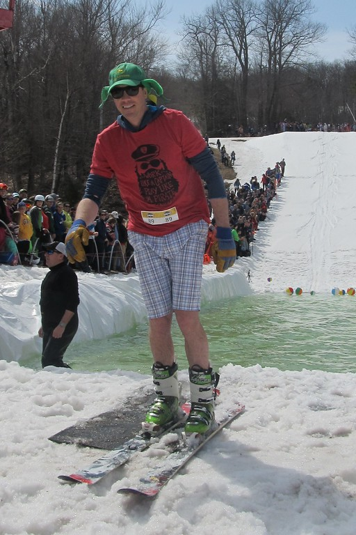 . VJ Donnelly of Westboro smiles after a successful run across the water during Wachusett Mountain\'s Pond Skim Festival on Sunday. SENTINEL & ENTERPRISE / Nick Mallard