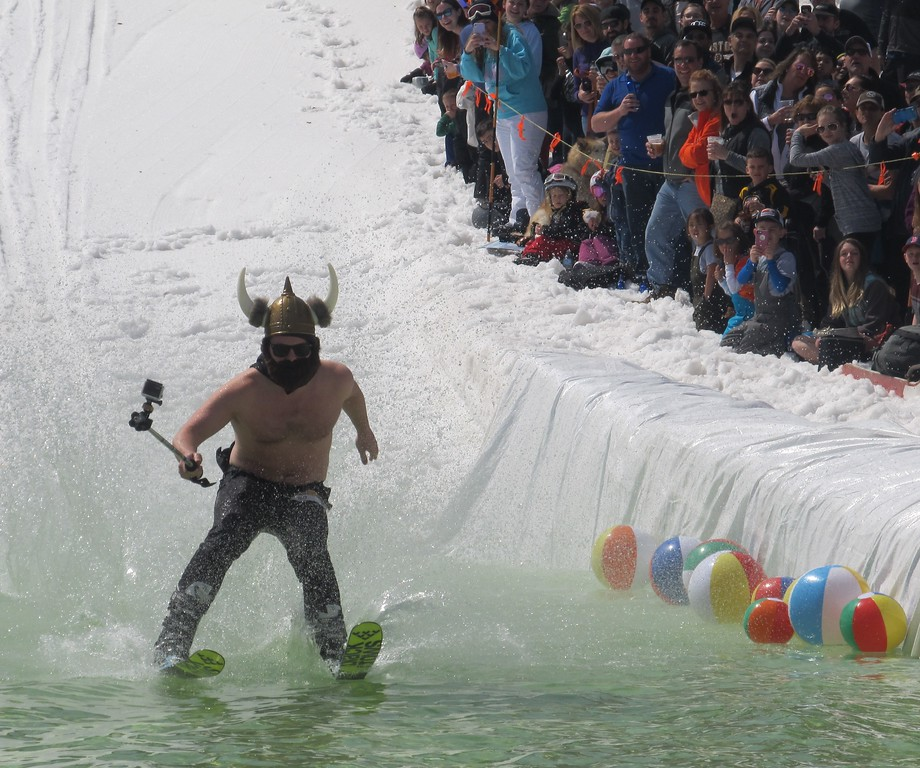 . With his GoPro in hand, Hudson\'s Tim Lawless makes his way across the water during Wachusett Mountain\'s Pond Skim Festival in Princeton on Sunday, April 7, 2019. SENTINEL & ENTERPRISE / Nick Mallard