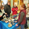 PHOTOS BY JENN SMITH — THE BERKSHIRE EAGLE <br /> Wahconah Regional High School National Honor Society chapter members Danni Orlando, left, and Aspen Burke, right, help guests pick out a handmade ceramic bowl to take home after taking part in the group's Empty Bowls dinner to benefit area food programs.