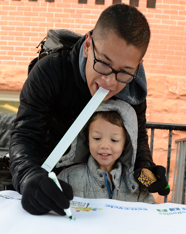 . BOULDER, CO - October 10, 2018: Miguel Sanchez (cq) and his son, Mico sign the walk/wheeled to school poster at University Hill Elementary in Boulder. Over 40 schools in the Boulder Valley School District (BVSD) joined in  Walk or Ride to School Day events at their schools. Students will be encouraged to walk or bike to school to build community, promote health, contribute to a cleaner planet and champion safer routes to school on October 10, 2018. (Photo by Cliff Grassmick/Staff Photographer))