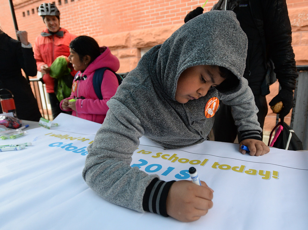 . BOULDER, CO - October 10, 2018:  Michael Quijada (cq) sign the walked and wheeled to school poster. Students from University  Hill Elementary in Boulder gather around the prize tents after walking or riding to school. Over 40 schools in the Boulder Valley School District (BVSD) joined in   Walk or Ride to School Day events at their schools. Students will be encouraged to walk or bike to school to build community, promote health, contribute to a cleaner planet and champion safer routes to school on October 10, 2018. (Photo by Cliff Grassmick/Staff Photographer))