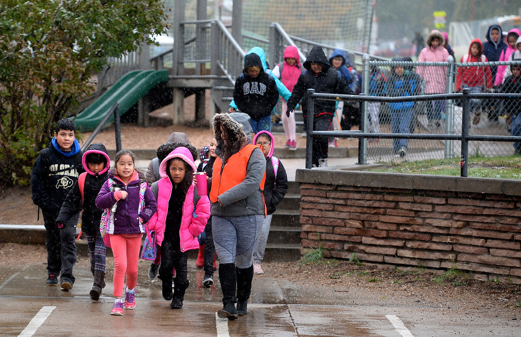 . BOULDER, CO - October 10, 2018:  Crossing guard, Alexandra Johnson, (cq) leads a large group of kids to University Hill Elementary in Boulder on Wednesday. Over 40 schools in the Boulder Valley School District (BVSD) joined in   Walk or Ride to School Day events at their schools. Students will be encouraged to walk or bike to school to build community, promote health, contribute to a cleaner planet and champion safer routes to school on October 10, 2018. (Photo by Cliff Grassmick/Staff Photographer))