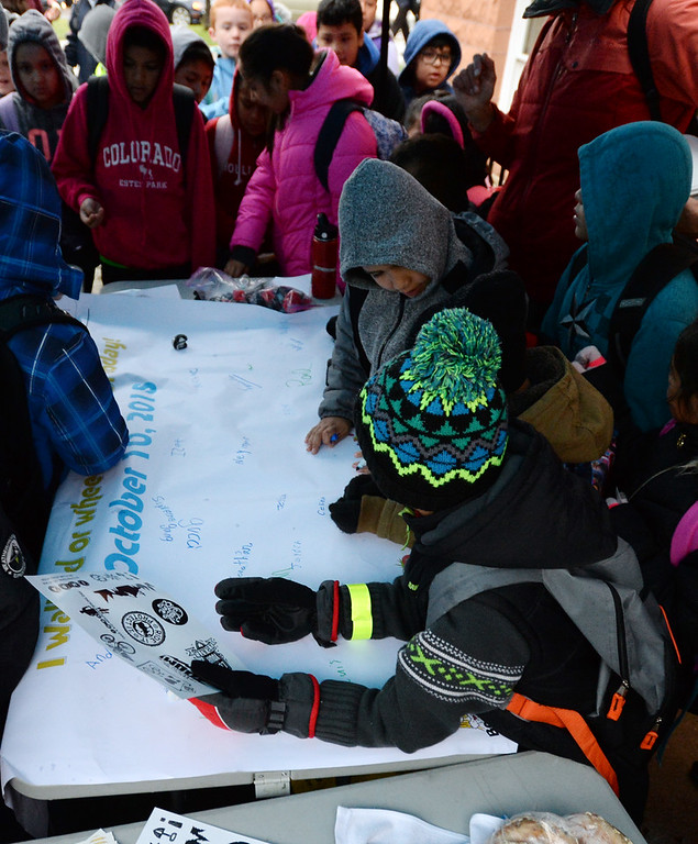 . BOULDER, CO - October 10, 2018:  Students from University  Hill Elementary in Boulder sign the poster at the prize tent after walking or riding to school. Over 40 schools in the Boulder Valley School District (BVSD) joined in   Walk or Ride to School Day events at their schools. Students will be encouraged to walk or bike to school to build community, promote health, contribute to a cleaner planet and champion safer routes to school on October 10, 2018. (Photo by Cliff Grassmick/Staff Photographer))