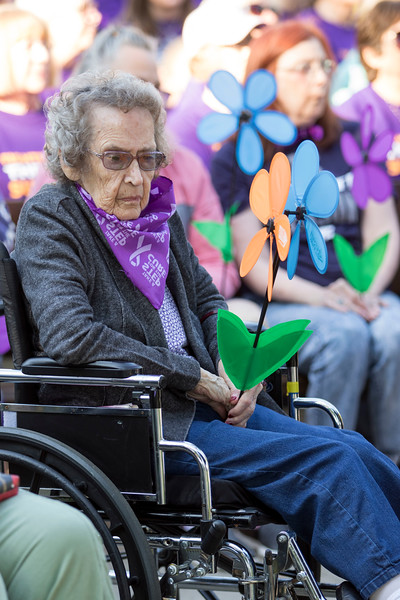 Members of the Manhattan Commuity gather at the Walk to End Alzheimer's on Sept. 14, 2019. An attendee of the walk holds a blue flower symbolizing they are living with Alzheimer's. ( Sabrina Cline | Collegian Media Group )