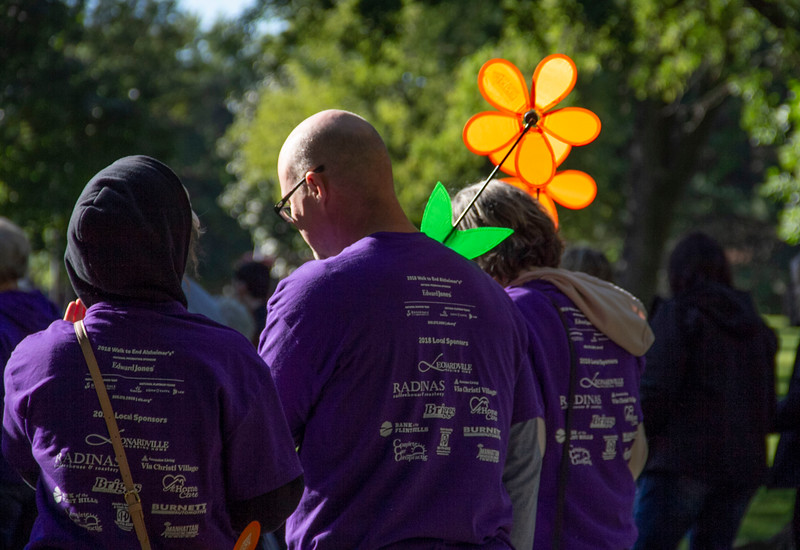 Participant at the Walk to end Alzheimer's holds up their Promise Flower during the walk. The orange flower represents that they support the cause and vision of a world without Alzheimer's. (Jessica Cude | Collegian Media Group)