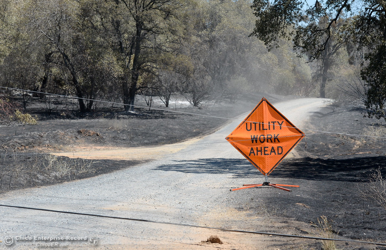 Downed power lines are seen along with utility work signs along a road near Viewcrest Drive due to the Wall Fire near Oroville, Calif. Mon. July 10, 2017. (Bill Husa -- Enterprise-Record)