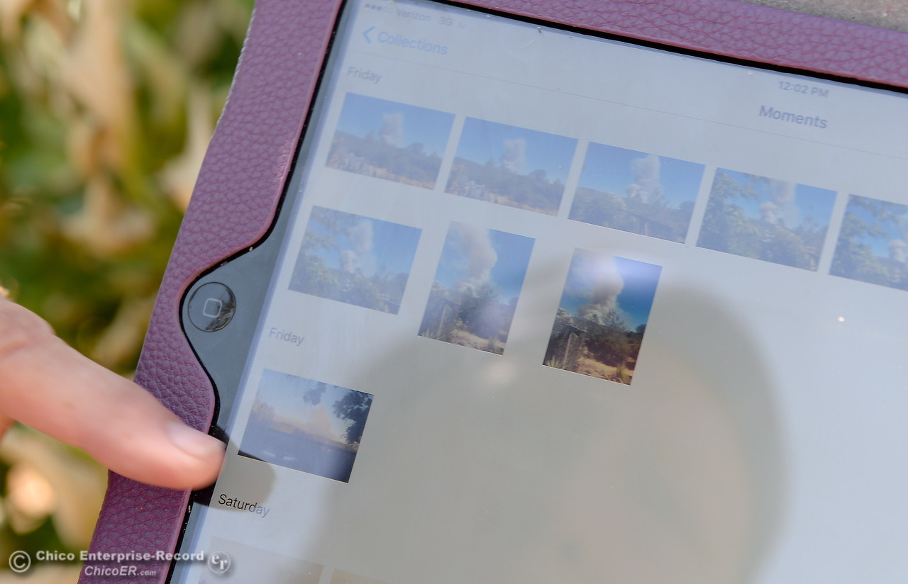 Cathy Prestella looks at photos she took of the the Wall Fire approaching her home near Oroville, Calif. Mon. July 10, 2017. (Bill Husa -- Enterprise-Record)