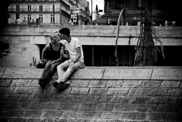A couple sitting along the Seine River in Paris enjoying ice cream and sharing a moment of love.