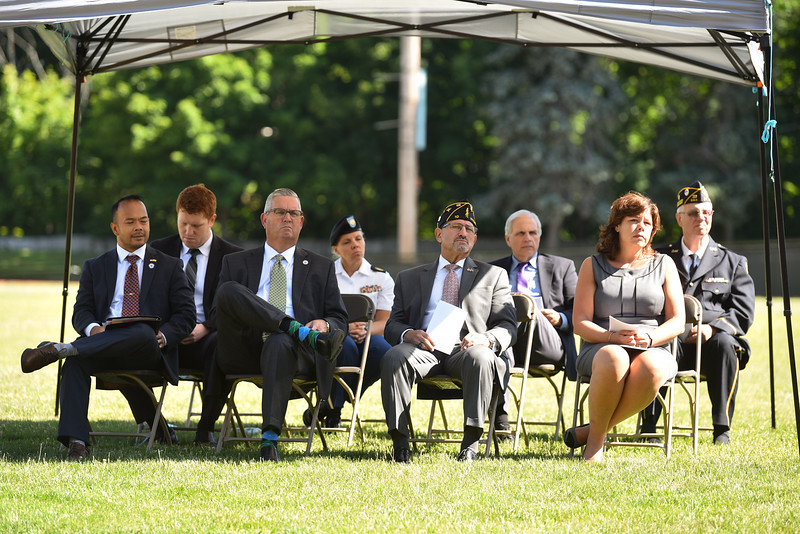 "Local officials sit under a tent after speaking to a crowd of Fitchburg Locals during a ceremony on Thursday at Crocker Field in Fitchburg commemorating ""The Wall That Heals.""  SENTINEL & ENTERPRISE JEFF PORTER"