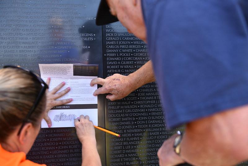 "Michelle Cote (left) of Fitchburg etches out the name of a fallen soldier who was a freind of local veteran Rudy Maki (right) during a ceremony on Thursday at Crocker Field in Fitchburg commemorating ""The Wall That Heals.""  SENTINEL & ENTERPRISE JEFF PORTER"