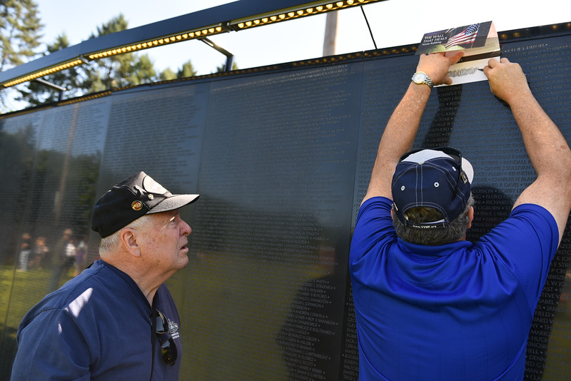"A man with ""The Wall That Heals"" etches out the name of a fallen soldier who was a freind of local veteran Rudy Maki (left) during a ceremony on Thursday at Crocker Field in Fitchburg commemorating ""The Wall That Heals.""  SENTINEL & ENTERPRISE JEFF PORTER"