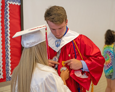 Olivia Beitz (left) helps Tanner Powers pin his medals to his gown before Wall High School held their Commencement Exercises for the Class of 2019 in their gymnasium on Thursday June 20, 2019. [ALYSSA RASP | THE COAST STAR]