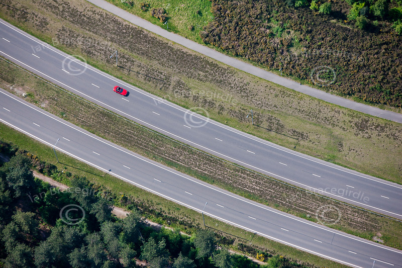 An aerial photo of a red sports car on an empty road.