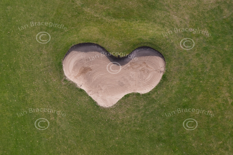 An aerial photo of a love heart shaped gold bunker.