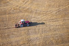 Aerial photo of a red tractor working in a field.