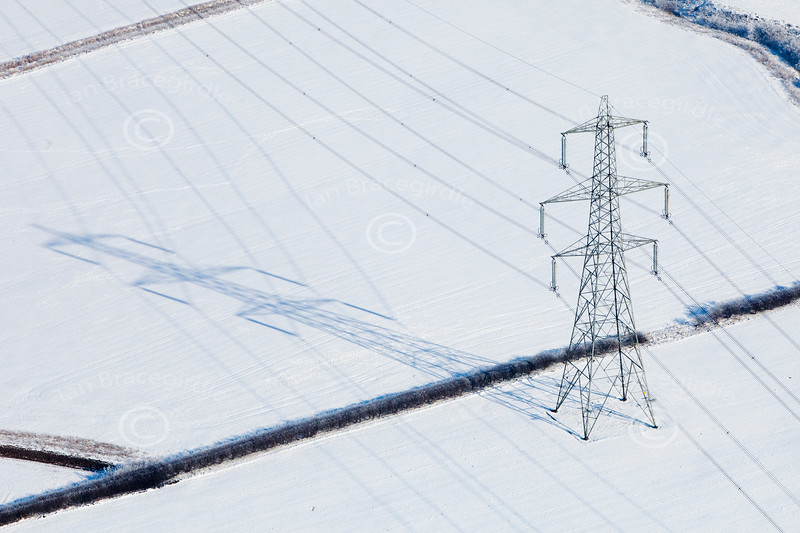 aerial photo of an electricity pylon and shadow in the snow.