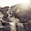 Waterfall, rocks, sun