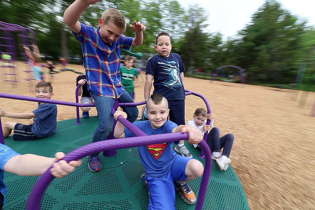 . Kids enjoy playing on the new equipment at Wallis Park Playground in Lunenburg during the ribbon cutting on Tuesday morning. The kids could not get enough of the new merry-go-round on the playground. Having fun on the merry-go-round is, from left, Wyatt Yost, 7, James Barrett, 10, and Maddox Hall, 7. SENTINEL & ENTERPRISE/JOHN LOVE