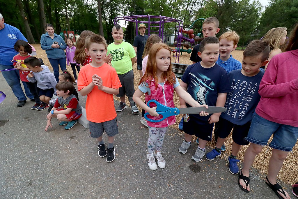 . Kids enjoy playing on the new equipment at Wallis Park Playground in Lunenburg during the ribbon cutting on Tuesday morning. Thersea Letarte, 7 holding big sissiors, cut the ribbon to official open the park at the small ceremony. SENTINEL & ENTERPRISE/JOHN LOVE