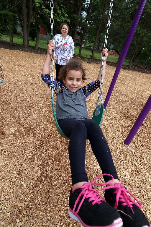 . Kids enjoy playing on the new equipment at Wallis Park Playground in Lunenburg during the ribbon cutting on Tuesday morning. being pushed on the swing by her aunt Ashley Shaw is Nya Shaw, 4, just after the ceremony. SENTINEL & ENTERPRISE/JOHN LOVE