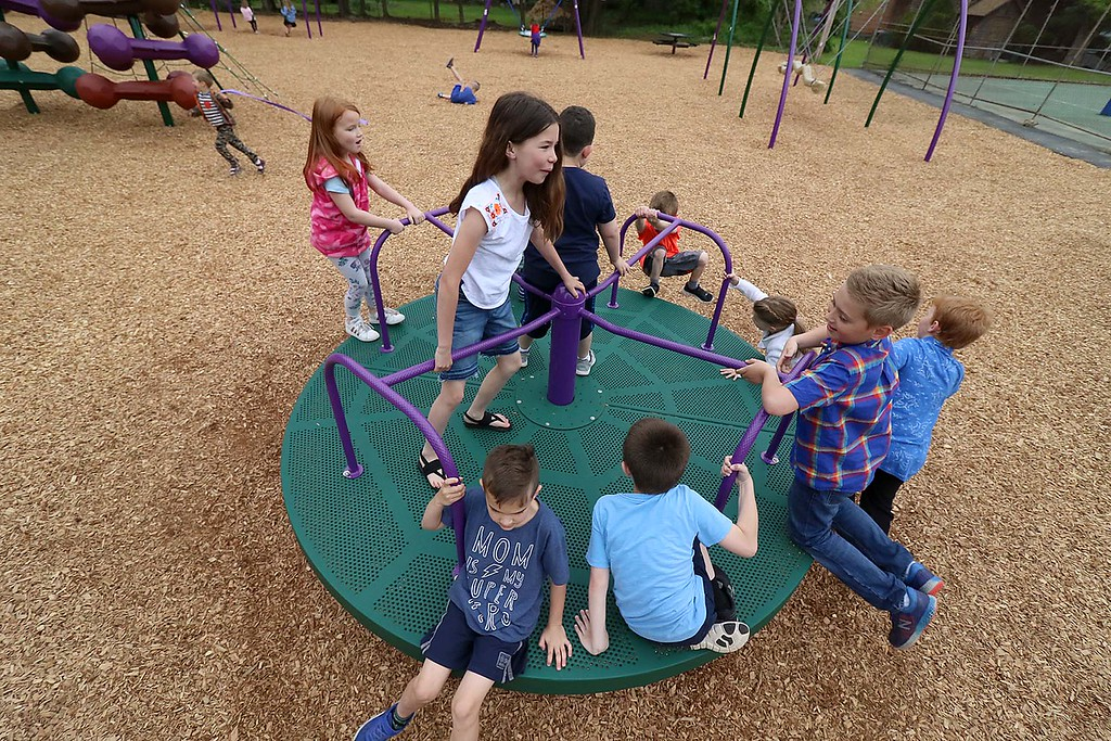. Kids enjoy playing on the new equipment at Wallis Park Playground in Lunenburg during the ribbon cutting on Tuesday morning. The kids could not get enough of the new merry-go-round on the playground. SENTINEL & ENTERPRISE/JOHN LOVE