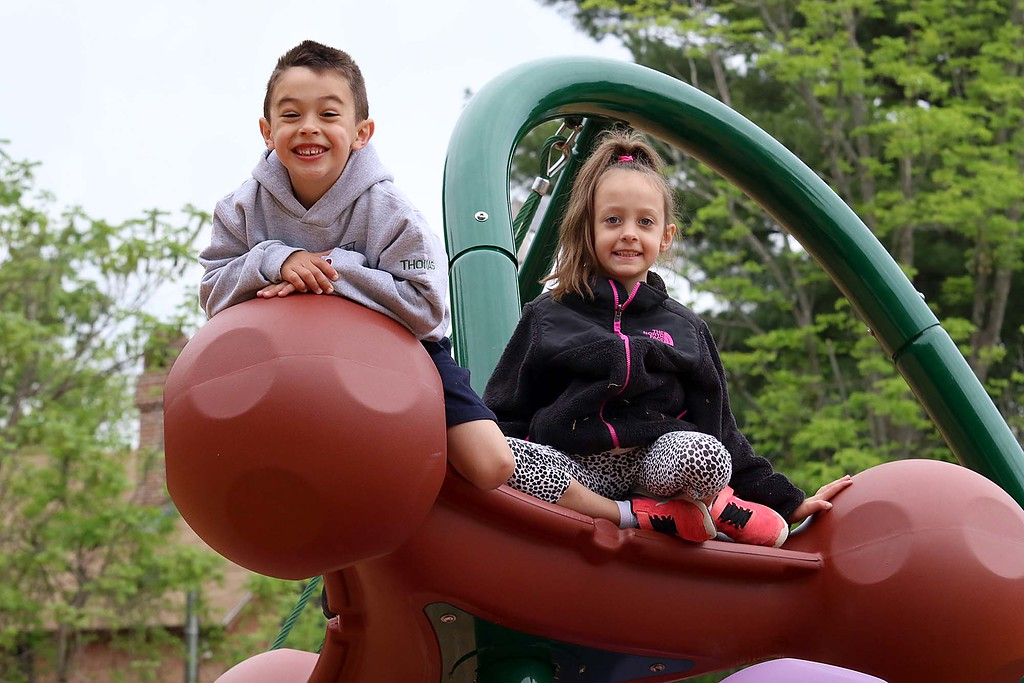 . Kids enjoy playing on the new equipment at Wallis Park Playground in Lunenburg during the ribbon cutting on Tuesday morning. Friends Thomas Letarte, 5, and Livia Hovey, 7, climb to the top of one of the new pieces in the park. SENTINEL & ENTERPRISE/JOHN LOVE
