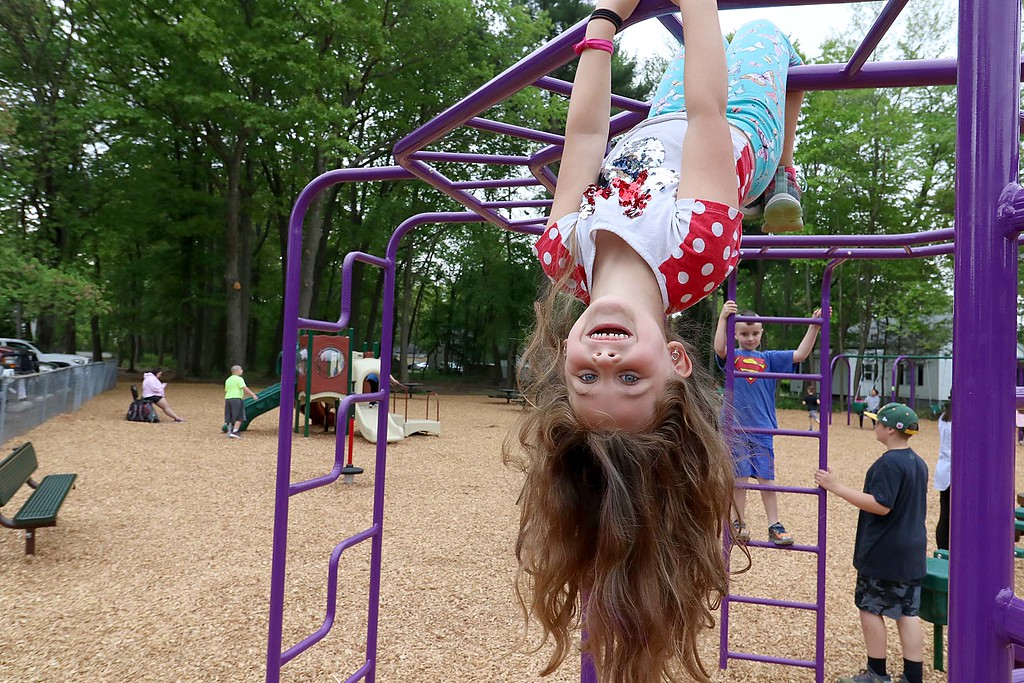 . Kids enjoy playing on the new equipment at Wallis Park Playground in Lunenburg during the ribbon cutting on Tuesday morning. Caylen St. George said she was acting lick a monkey as she hung upside down on the monkey bars in the park. SENTINEL & ENTERPRISE/JOHN LOVE