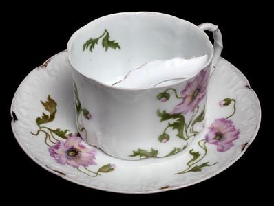 Tasse et sous-tasse protège-moustache en porcelaine de Bavière à motif floral, début du 20e siècle.