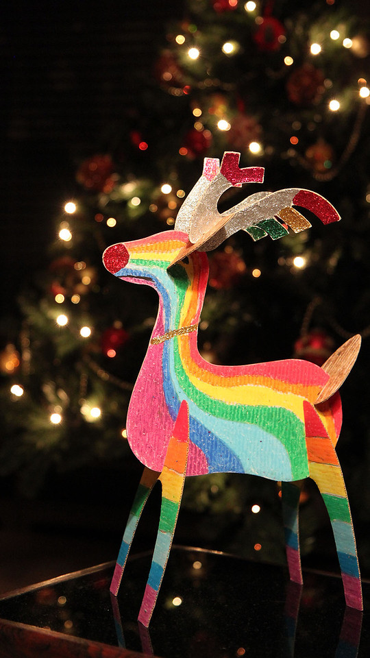 A paper crafted reindeer with a Christmas tree