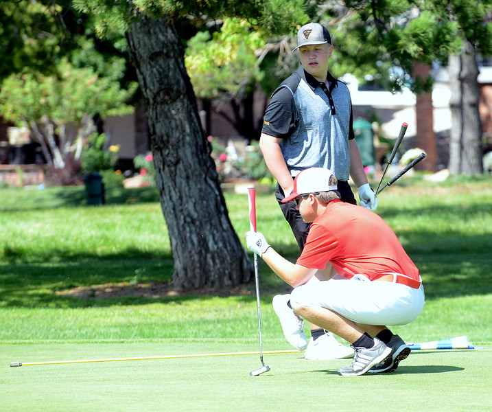 Loveland's Lauden Jones lines up his putt as Thompson Valley's Dylan Malone walks aroun dto get a read on his attempt during the Walt Clark Invitational on Wednesday at the Olde Course in Loveland. (Mike Brohard/Loveland Reporter-Herald)