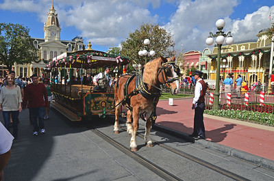 Horse drawn trolly at the Magic Kingdom in front of train station.